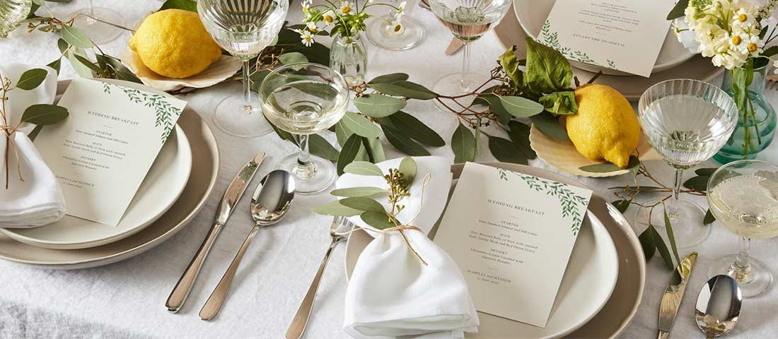 beautiful wedding tablescape with green floral menu wedding stationery and champagne coupes with lemons on the table