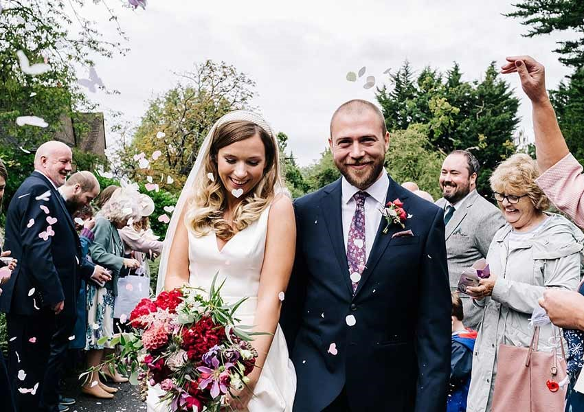 wedding day photography confetti moment with the bride and groom surrounded by guests
