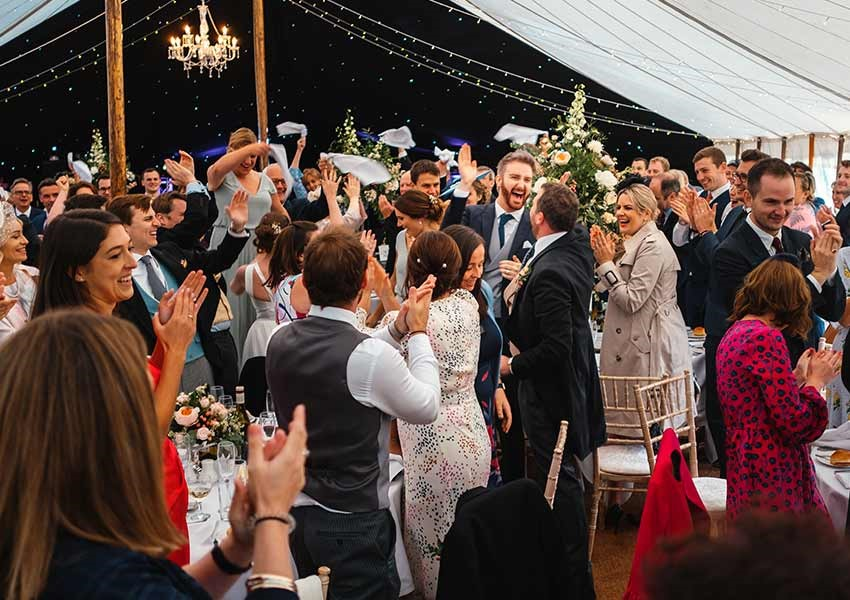 Marquee wedding outdoors in summer with wedding guests clapping and celebrating
