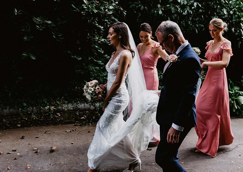 Bride walking into church with bridesmaids and father of the bride