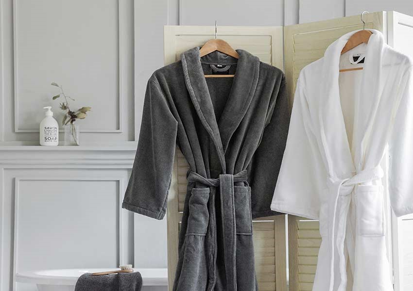 Bathrobes hanging on a bathroom door from A by Amara at The Wedding Shop
