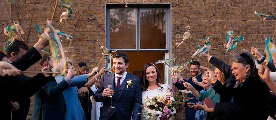 Newly wedded couple walking out the church with family and friends