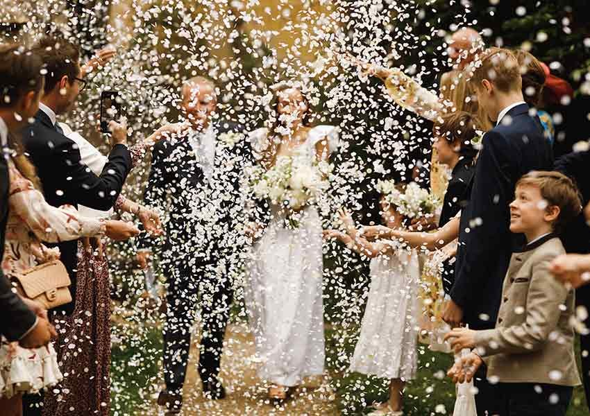 newly married couple being showered with confetti