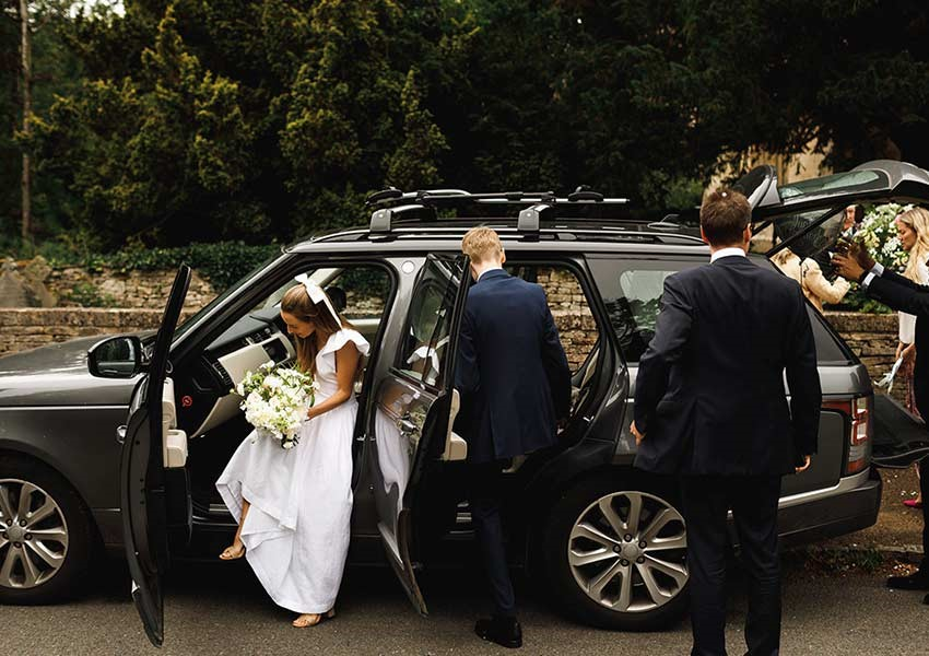 bride stepping out of wedding car