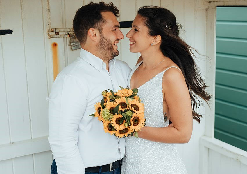 wedding shop couple with sunflowers on the beach
