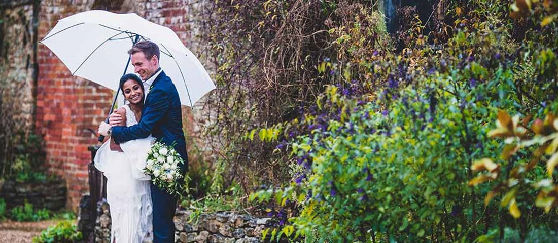 Couple on wedding day in the rain with white umberlla
