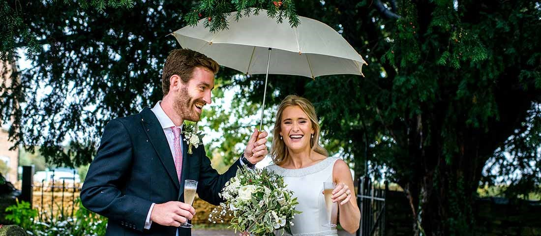 Happy couple celebrating their wedding in the rain