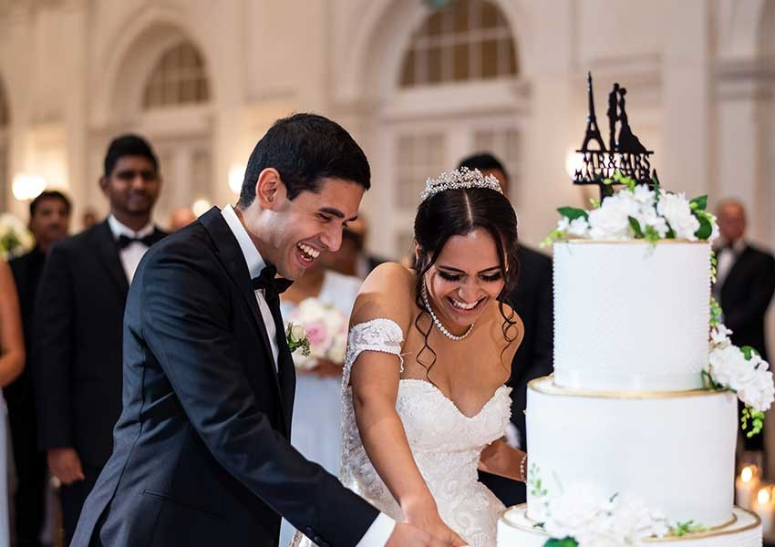Couple cutting 4 tier wedding cake
