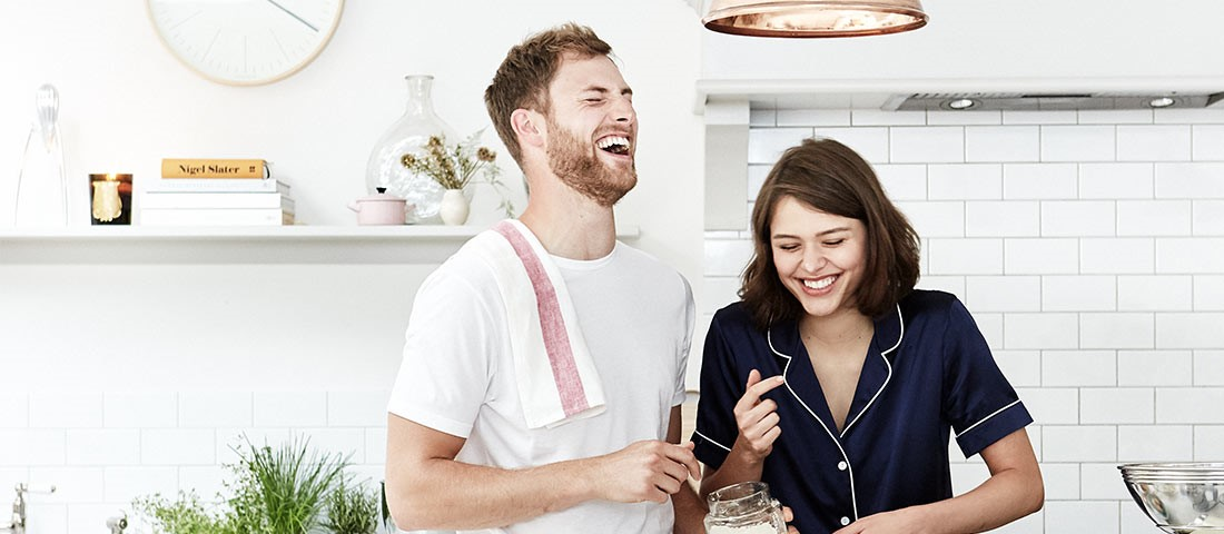 couple cooking breakfast with wedding registry gifts