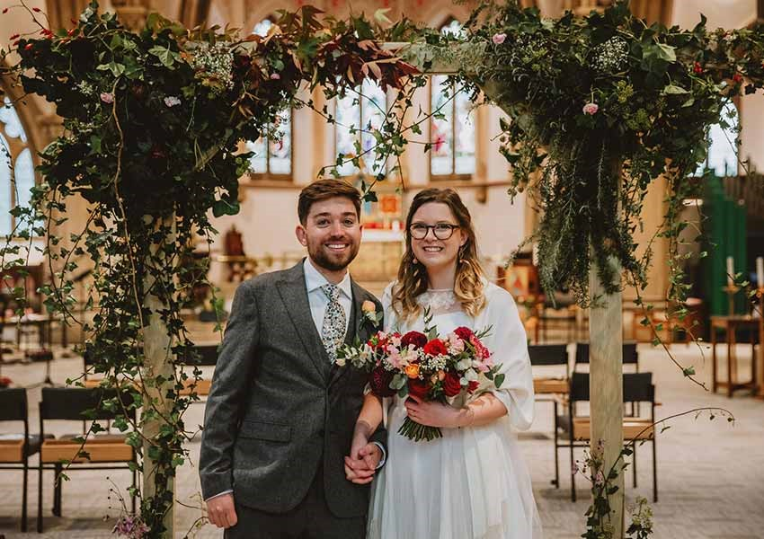 London wedding with bright bridal bouquet and foliage red and orange roses