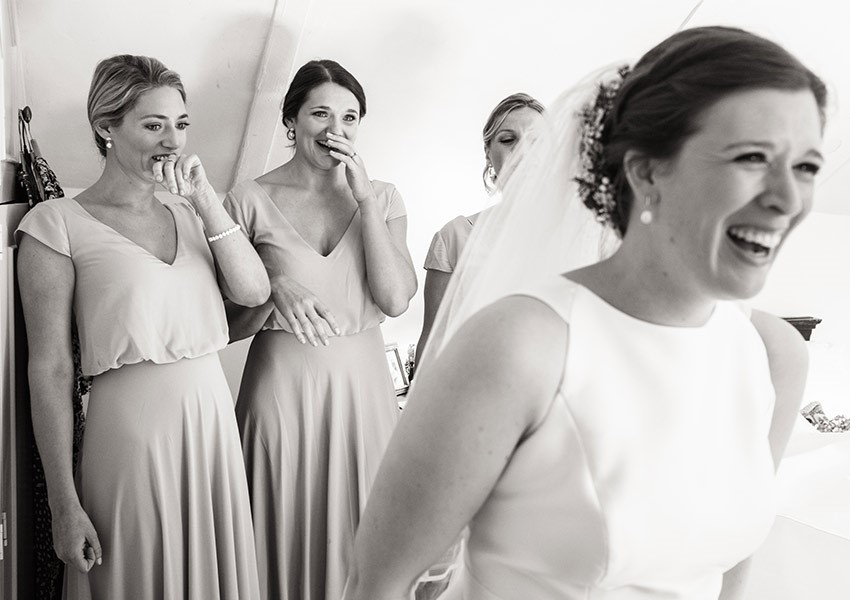 Bride smiling with her bridesmaids on her wedding day