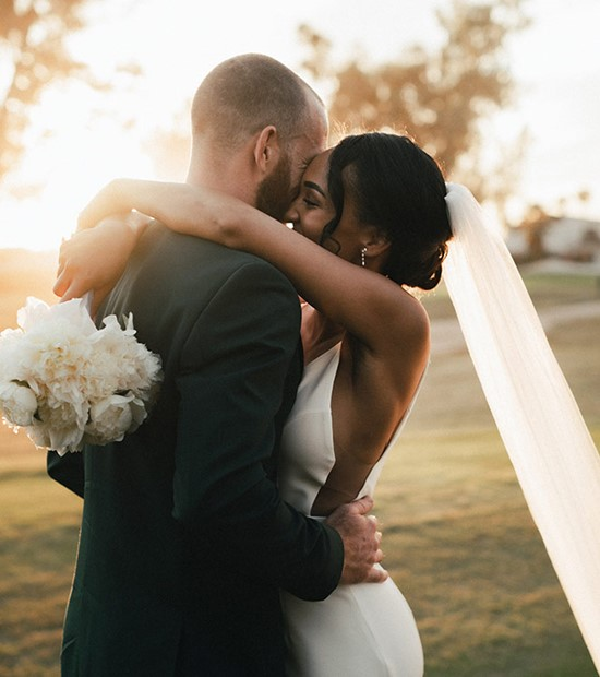 Bride and groom holding each other at sunset