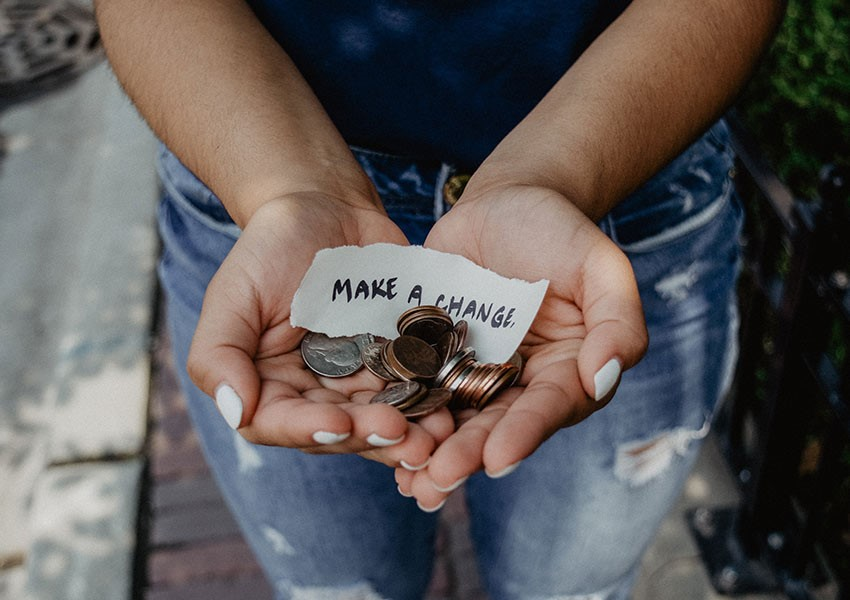 make a change woman holding money in her hands with a note saying make a change