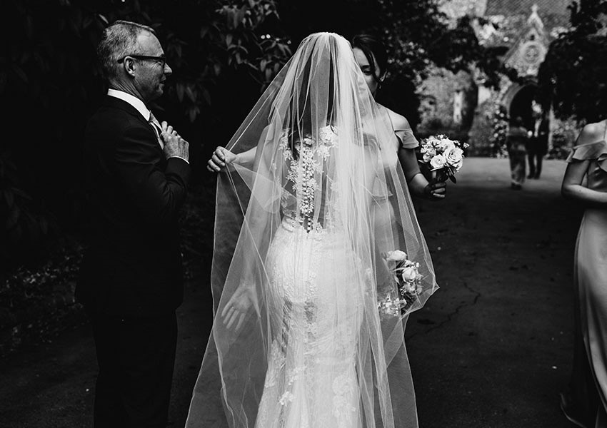 Black and white wedding day photography - bride wears long sweeping vile and lace embellished back wedding dress