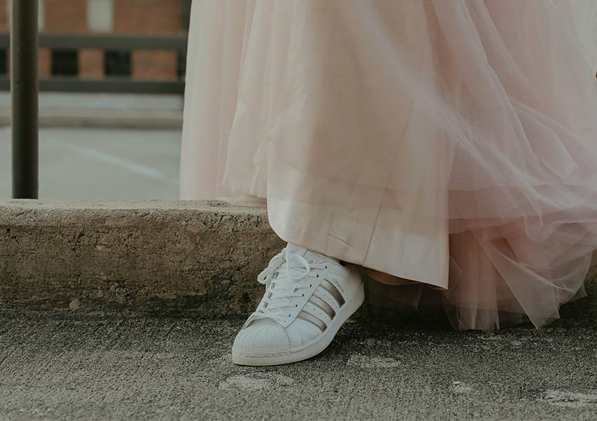 person walking into the street wearing white trainers and pink tulle skirt