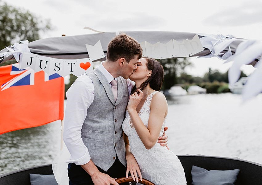 bride and groom kissing on boat wedding