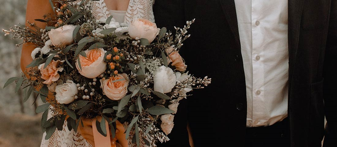 wedidng flowers checklist - bride and groom holding hands with peach and white rose wedding bouquet