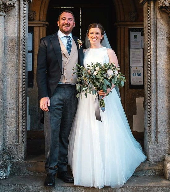 Bride and groom stood outside church smiling
