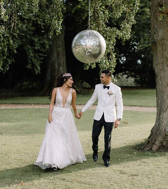 Bride and groom outside Aynhoe Park with disco ball in the trees