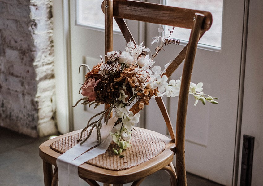 white and pink flowers on rustic wooden chair