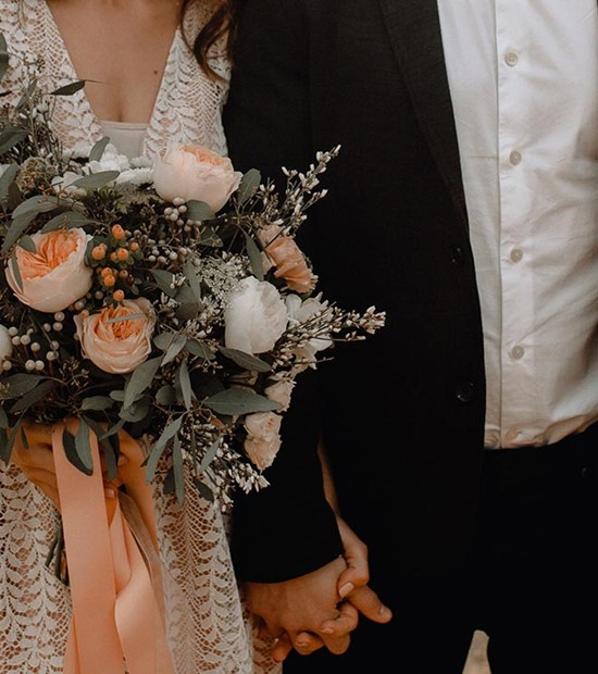 bride and groom holding hands, bride holds peach and white wedding bouquet