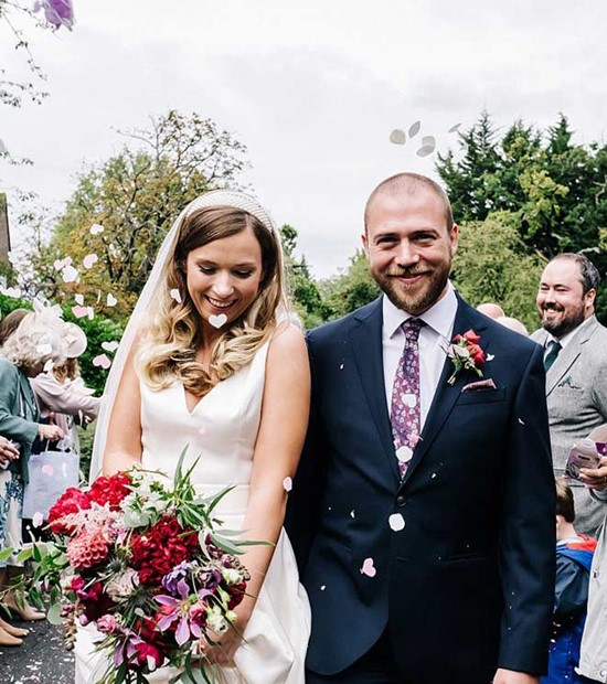 bride and groom confetti moment with bright pink and purple wedding flowers