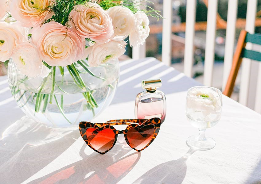 heart sunglasses on outdoor table with wine, perfume and flowers