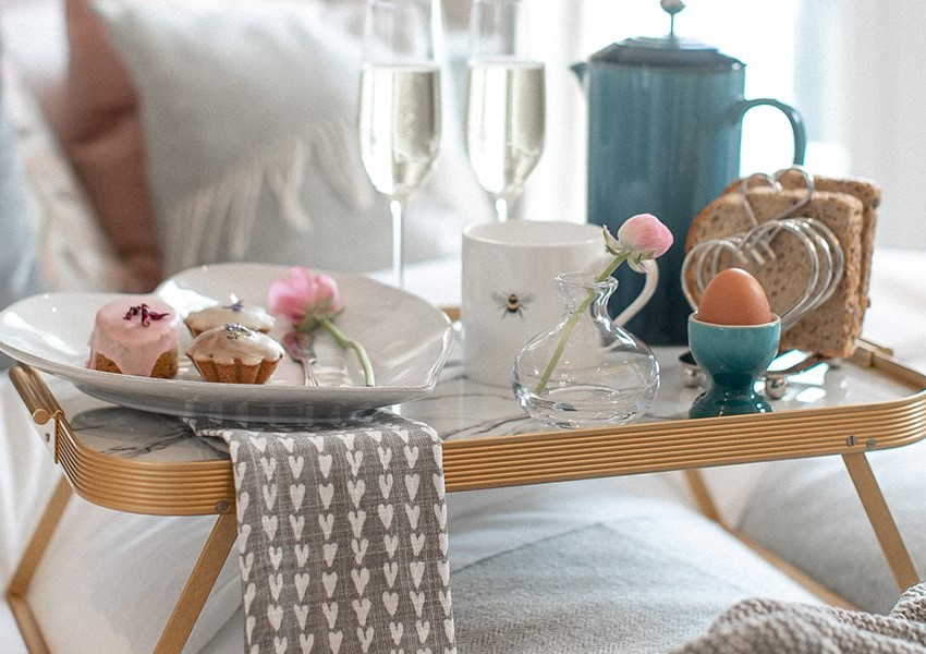Breakfast in bed tray with champagne cake and egg cups
