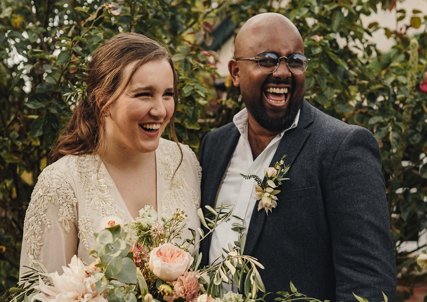 Newly wed couple laughing for backyard wedding